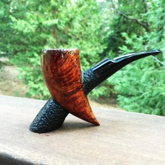 Handmade briar tobacco pipe with smooth and textured surfaces. Features a hand cut German ebonite stem.